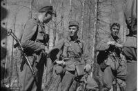 """Kolme huimapäätä ja kovien taistelujen karaisemaa upseeria neuvottelussa ennen vastaiskua. Kuvassa vasemmalla kapteeni Railio JR 33, keskellä Mannerheim-ristin ritari luutnantti Törni Jääkärikomppanian päällikkö ja oikealla edellisen """"""""adjutantti"""""""" luutnantti Pitkänen."""
